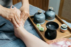 Image of a student practicing the skills they have learned in the living essentials certified foot reflexology course.